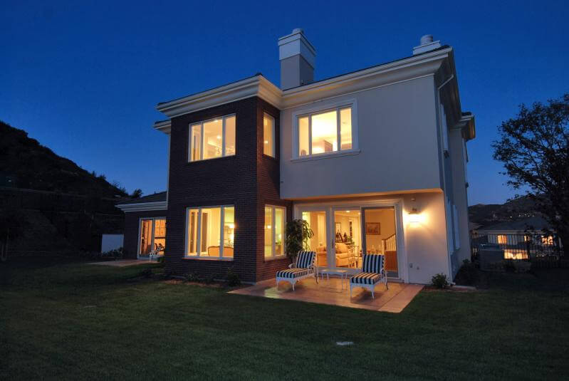 House with large windows and glass doors, equipped with security systems